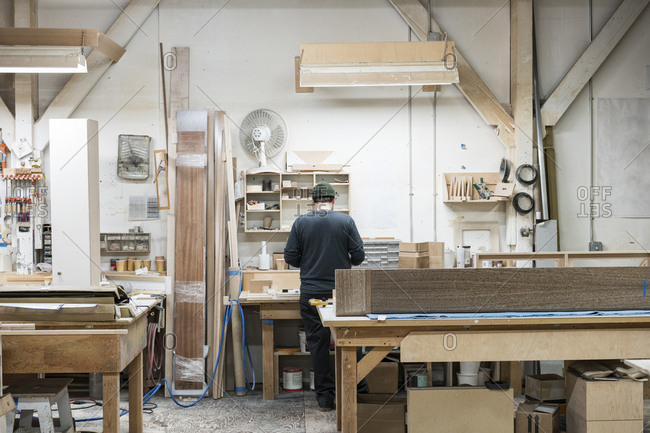 Carpenter working on a cabinet project at his work station in a furniture factory