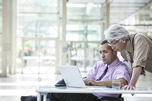 An Asian businessman and Caucasian businessman working on laptop computer in the lobby of a convention centre