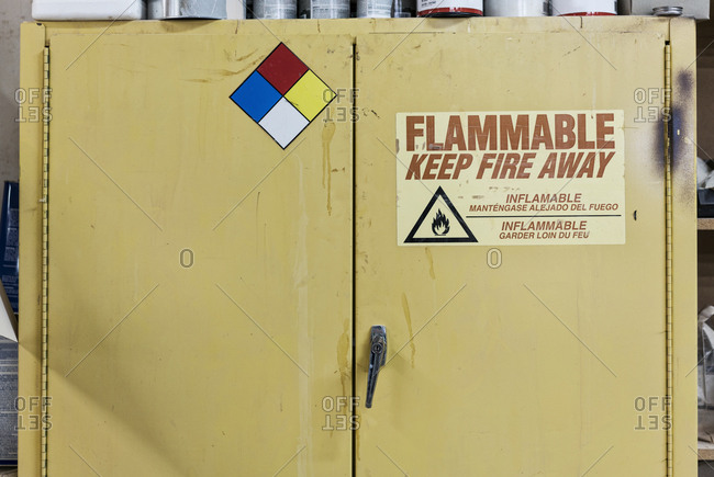 Safety sign reminders mounted to a metal cabinet in a woodworking factory