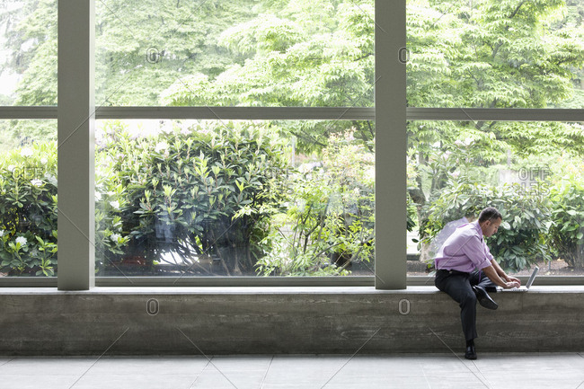 Businessman working on a notebook computer in front of a large window in a convention centre