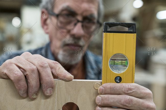 A senior man with glasses and beard in a woodworkers shop, using a spirit level checking his work