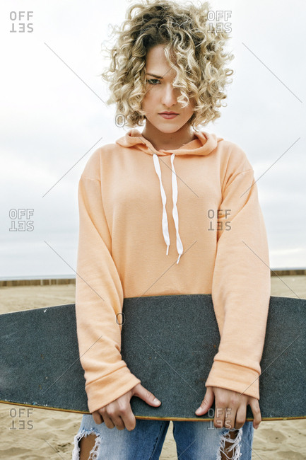 Young woman with curly blond hair wearing pink hoodie and ripped jeans standing on sandy beach, holding skateboard, looking at camera