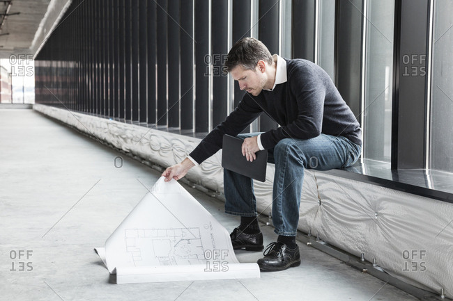 A Caucasian male architect working on building plans in a new raw business space