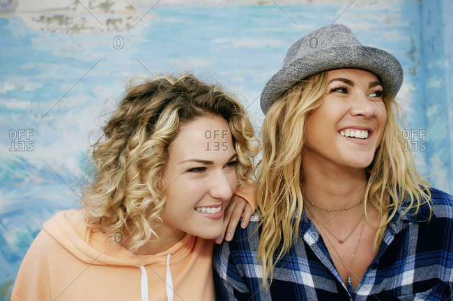 Portrait of two smiling women with blond hair wearing pink hoodie, blue checked shirt and grey Trilby hat