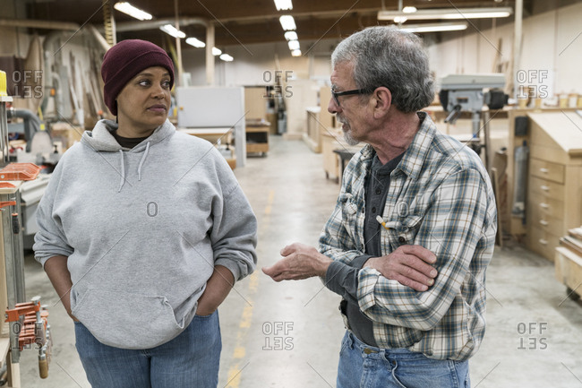 A senior caucasian male carpenter and a Black female carpenter discussion a project in a large woodworking factory