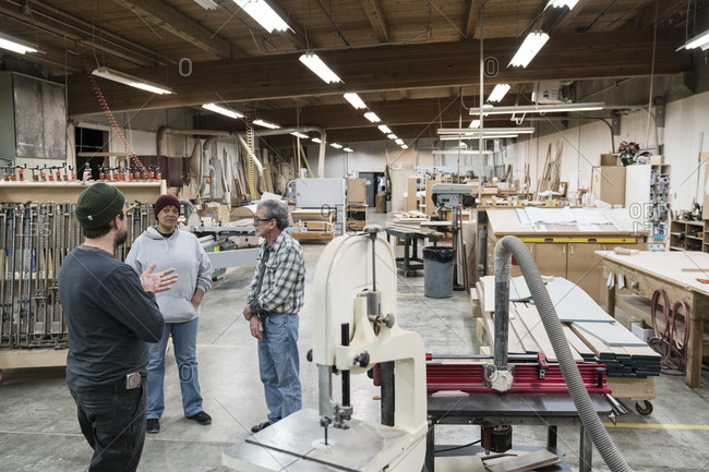 A group of mixed race carpenters discussing a project at a work station in a large woodworking shop