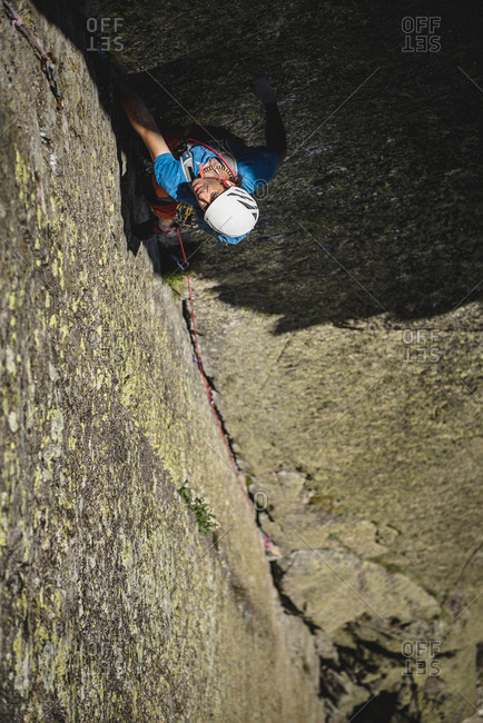 Mid aged climber wearing helmet climbing a dihedral crack on granite wall