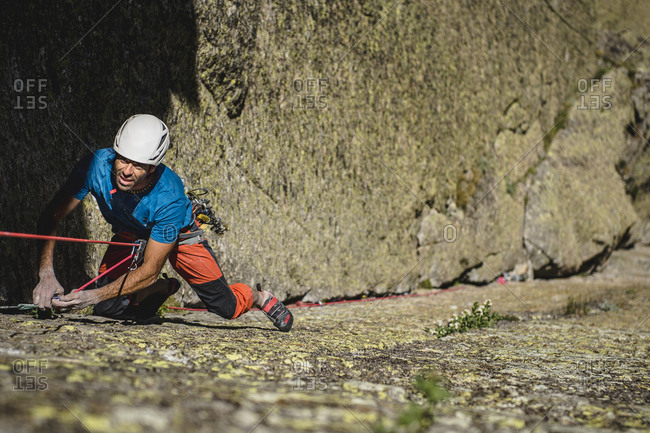 Mid aged climber wearing helmet rappelling on granite wall