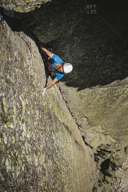 Mid aged climber wearing helmet climbing a dihedral crack on granite wall in traditional style