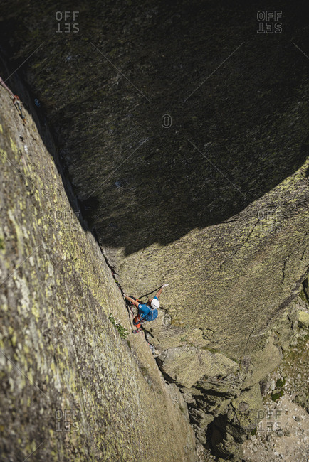 Rock climber wearing helmet climbing a dihedral crack on granite wall