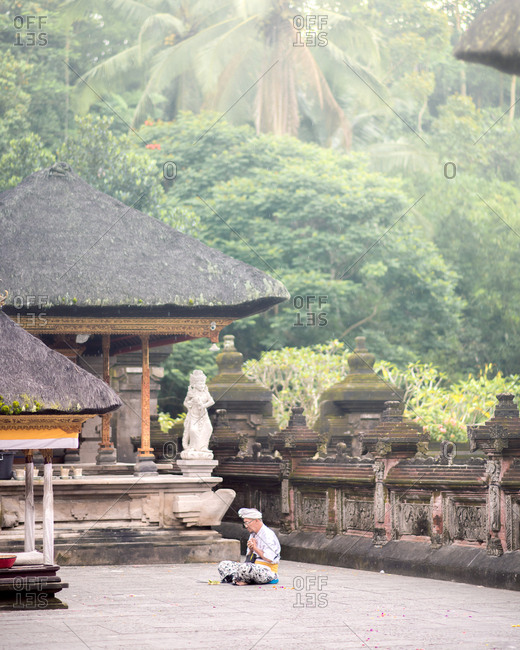 Bali, Indonesia - March 18, 2018: Balinese man doing a prayer at Tampak Siring Temple