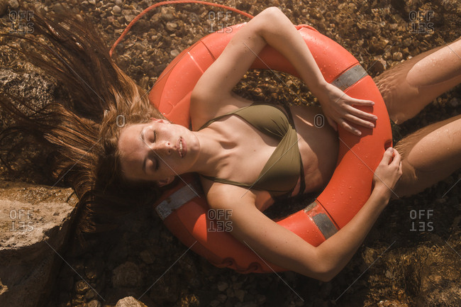 Young girl with a lifebelt lying and relaxing on the water of the river on a sunny summer afternoon