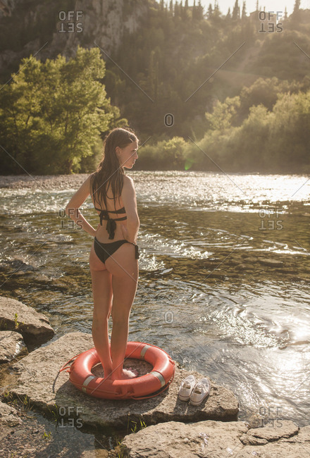 Young girl with a lifebelt relaxing on the riverbank on a sunny summer afternoon