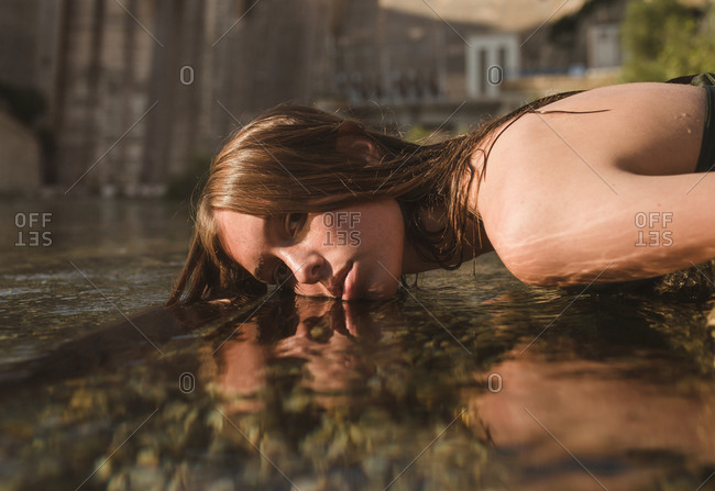 Young blonde girl with freckles lying on the bank of the river putting her head under the water