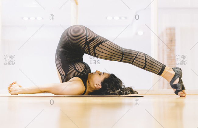 Woman lying and stretching on floor