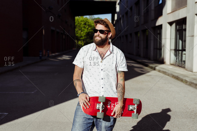 Handsome bearded and tattooed young man standing on the street and holding a skateboard