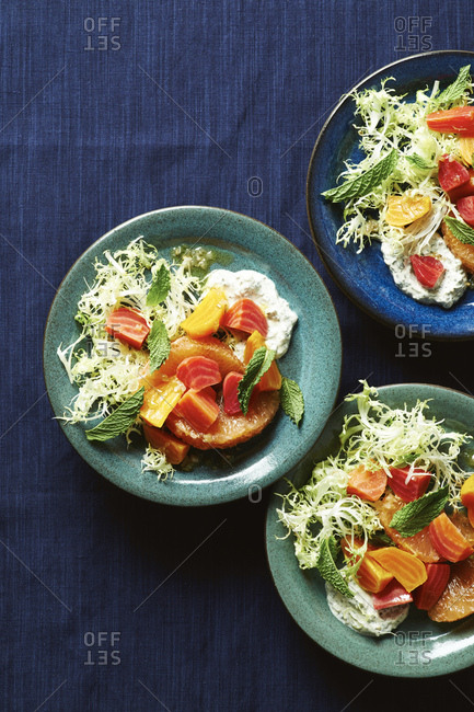 Three plates of colorful beet and grapefruit frisee salad