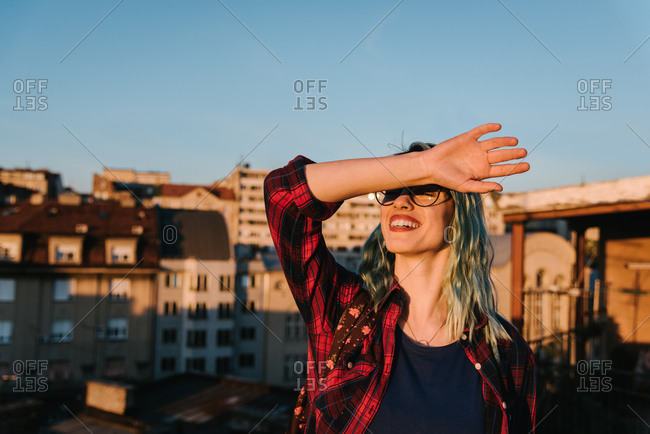 Smiling young attractive woman trying to look in a sunset by covering her eyes with her arm
