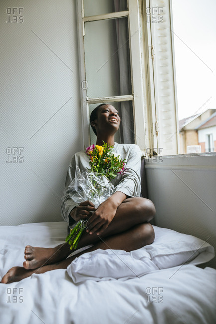 Woman with bouquet sitting on bed next to the window in her room