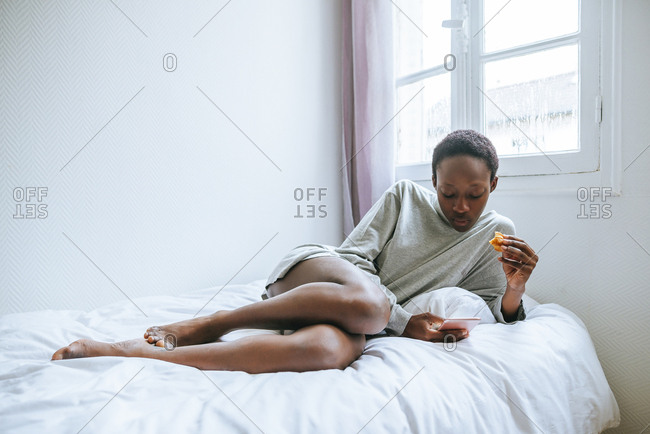 Woman using cell phone lying on the bed in her room