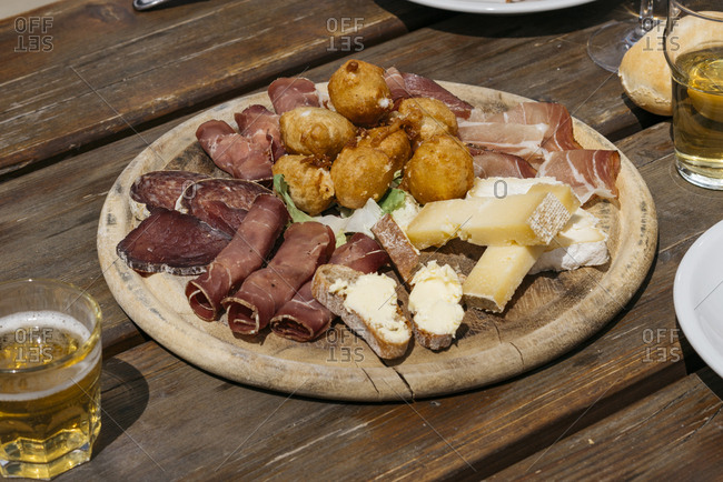 Antipasto with meats and cheeses served on wooden board