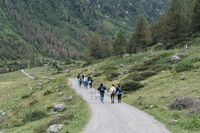 Livigno, Italy - July 12, 2018: People walking on gravel road through the Italian Alps