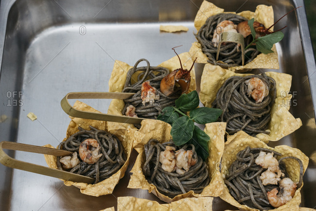 Individual pasta nests topped with shrimp served in crispy edible bowls