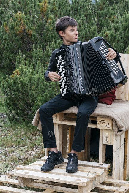 Livigno, Italy - July 12, 2018: Young man sitting on wooden crates playing button accordion