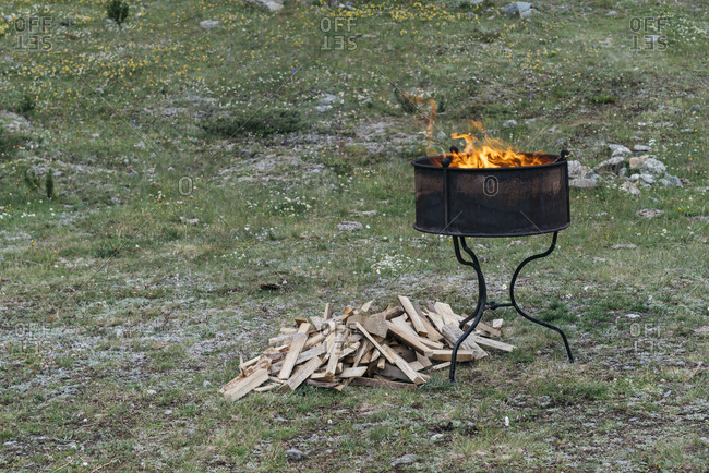 Fire pit on a stand with firewood