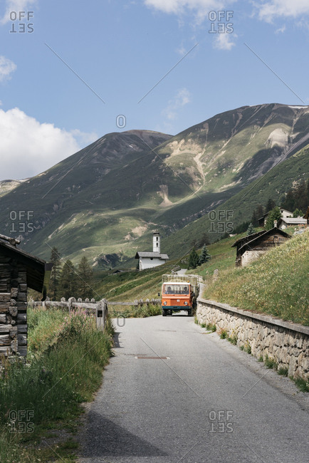Livigno, Italy - July 12, 2018: Truck driving on one lane mountain road through village in the Italian Alps