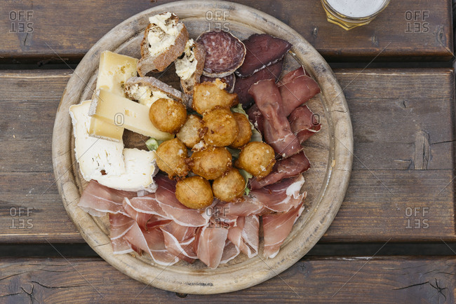 Antipasto with a variety of meats and cheeses served on round wooden board