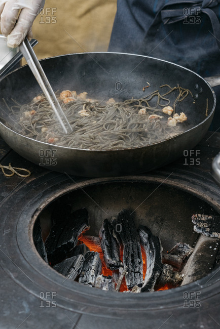 Person cooking pasta in skillet over hot embers