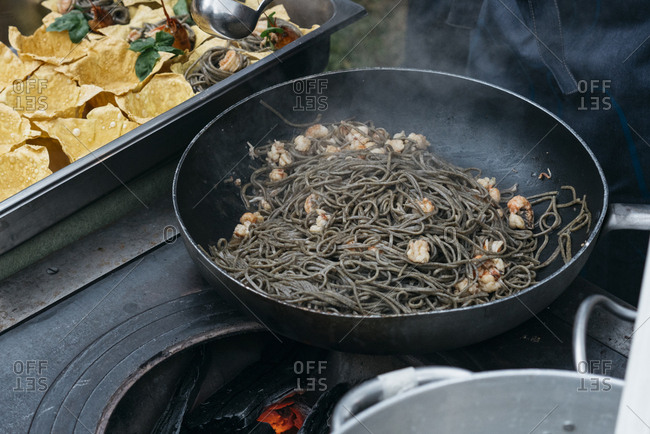 Pasta with shrimp cooked in a skillet over hot embers