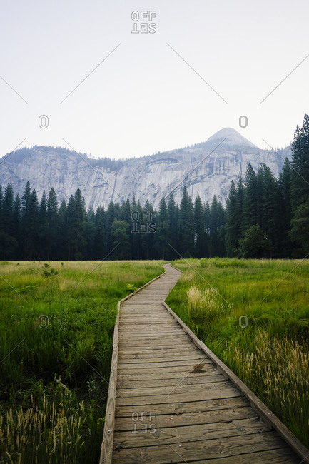 Boardwalk amidst grassy field in scenic mountains at Yosemite National Park against sky