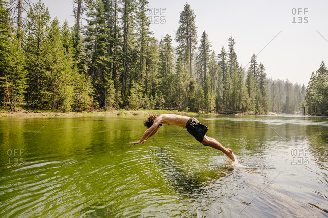 Full length of man diving in river by trees at Yosemite National Park