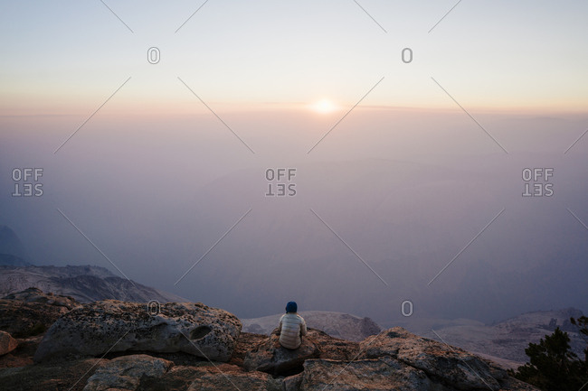 High angle view of hiker sitting on cliff by mountains in Yosemite National Park against sky during sunset