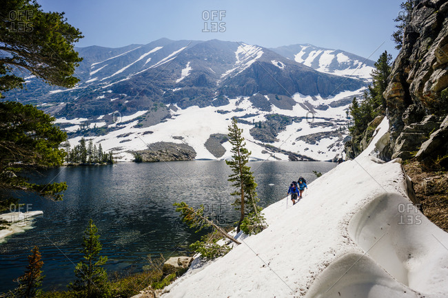 Hikers hiking on snow covered mountain by river at Sequoia National Park