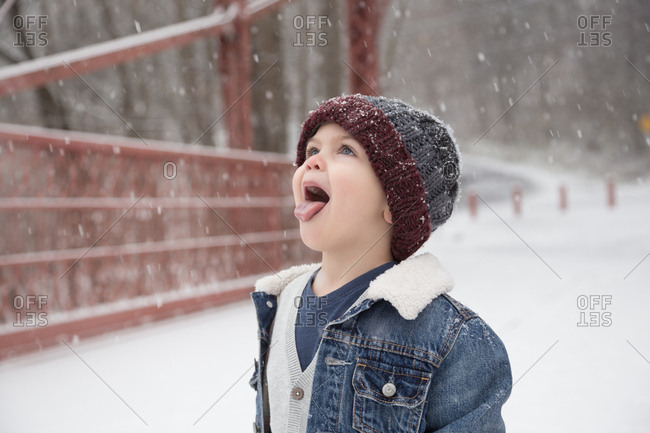 Little Boy Trying To Catch Snowflakes On Tongue