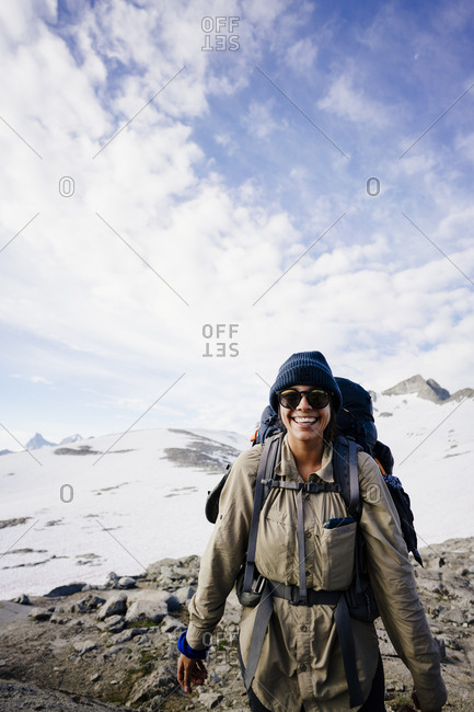 Portrait of smiling female hiker with backpack standing on snow covered mountain against sky