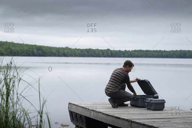 Mid adult male photographer opening suitcase on pier over lake against sky