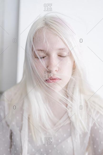 Woman with bleach blonde hair eyes closed