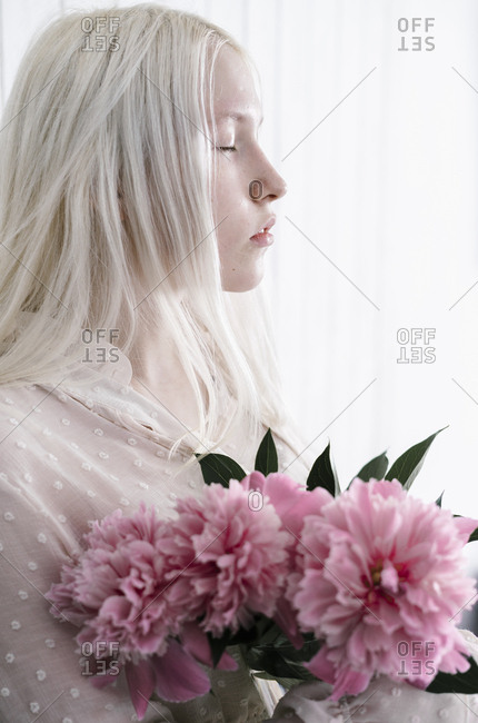 Side view of woman with bleach blonde hair holding pink flower