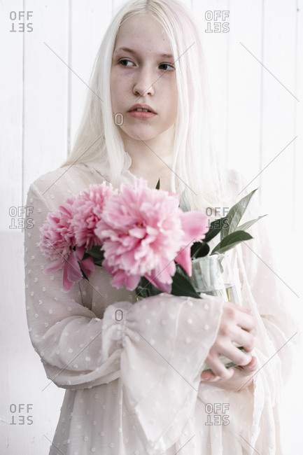 Woman with bleach blonde hair holding pink flower