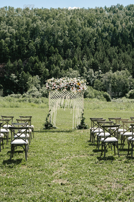 Wedding ceremony with arbor and wooden chairs