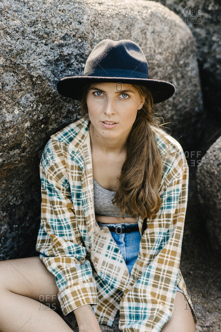 Young woman sitting on boulder in the Stolby Nature Sanctuary