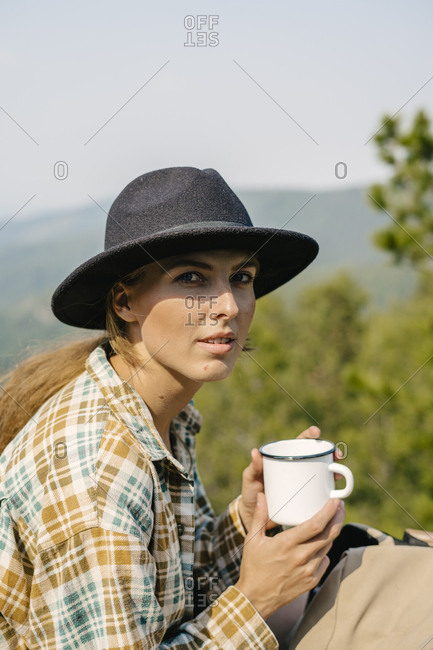 Young woman drinking coffee in the Stolby Nature Sanctuary