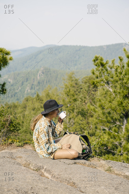 Young woman sitting on cliff enjoying coffee in the Stolby Nature Sanctuary