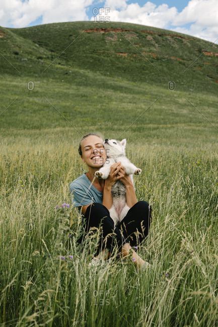 Woman cuddling with Siberian Husky puppy in a field