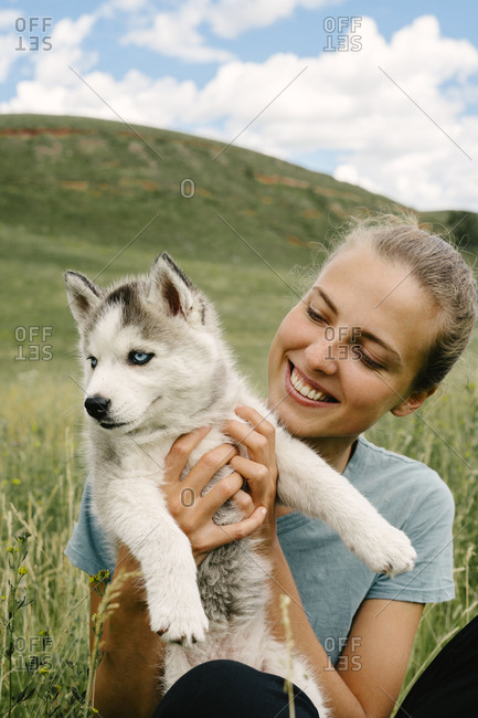 Young woman holding Siberian Husky puppy in a field