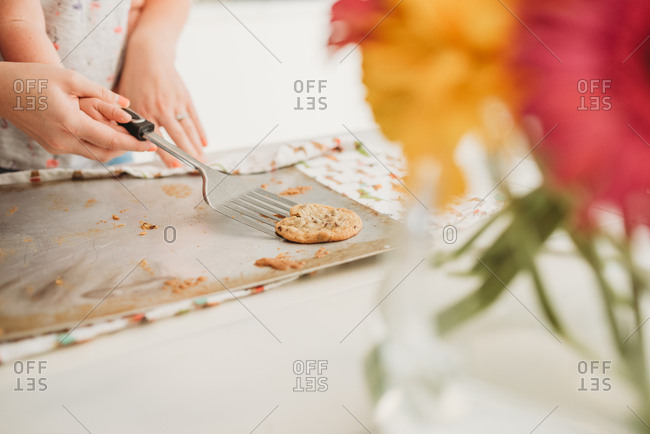 Mother helping daughter remove cookie from pan